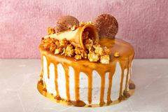 Delicious homemade cake with caramel sauce and popcorn on table Royalty Free Stock Images