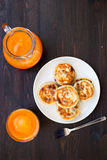 Delicious homemade cheese pancakes with fresh carrot juice Stock Images