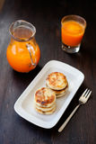 Delicious homemade cheese pancakes with fresh carrot juice Stock Photos