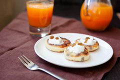 Delicious homemade cheese pancakes with fresh carrot juice Royalty Free Stock Photos