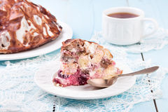 Delicious homemade cherry cake with cup of tea on wooden table. Delicious homemade cherry cake with white cup of tea. Close-up Royalty Free Stock Photos