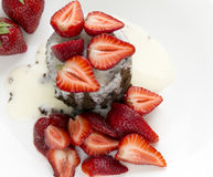 Delicious homemade chocolate cake with fresh red strawberries and cream sauce on white plate. Stock Photos