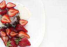 Delicious homemade chocolate cake with fresh red strawberries and cream sauce on white plate. Royalty Free Stock Photo