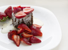 Delicious homemade chocolate cake with fresh red strawberries and cream sauce on white plate. Stock Image