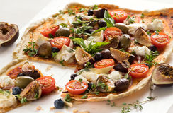 Delicious Homemade Flatbread Pizza. Homemade flatbread pizza with tomato,basil,fig,blueberries,cheese,olives and herbs. Close up stock photography