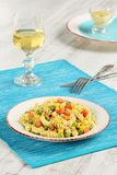 Delicious homemade fusilli pasta cooked with basil pesto, carrots, corn and peas in a plate on a turquoise blue napkin, served wit Royalty Free Stock Image