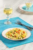Delicious homemade fusilli pasta cooked with basil pesto, carrots, corn and peas in a plate on a turquoise blue napkin, served royalty free stock photos