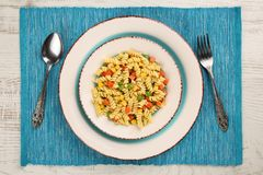 Delicious homemade fusilli pasta cooked with basil pesto, carrots, corn and peas in a plate on a turquoise blue napkin stock image
