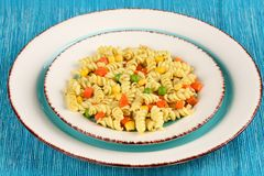 Delicious homemade fusilli pasta cooked with basil pesto, carrots, corn and peas in a plate on a turquoise blue napkin Stock Photography