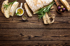 Delicious homemade italian ciabatta bread with olive oil and olives on wooden rustic background, above view, space for text royalty free stock image