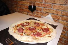 Delicious homemade Italian Pepperoni Pizza with a glass of red wine. In a restaurant royalty free stock image