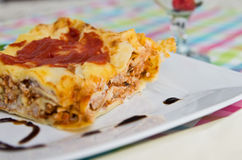 Homemade lasagna on white plate and colorful tablecloth Royalty Free Stock Image