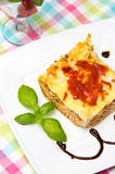 Homemade lasagna on white plate and colorful tablecloth Royalty Free Stock Photo