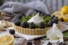 Delicious homemade lemon tart. Pie on rustic white table. Tart with blackberry and meringue Royalty Free Stock Photography