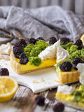 Delicious homemade lemon tart. Pie on rustic white table. Tart with blackberry and meringue Royalty Free Stock Image