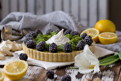 Delicious homemade lemon tart. Pie on rustic white table. Tart with blackberry and meringue Stock Image