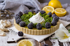 Delicious homemade lemon tart. Pie on rustic white table. Tart with blackberry and meringue Stock Photos