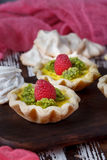 Delicious homemade lemon tart. Pie on rustic white table. Tart with raspberries and meringue Stock Photo