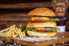 Delicious Homemade Maxi Burger with grilled beef steak, lettuce, cheese, tomato, onion, barbecue sauce, honey mustard, fries, pick Royalty Free Stock Image