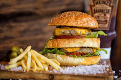 Delicious Homemade Maxi Burger with grilled beef steak, lettuce, cheese, tomato, onion, barbecue sauce, honey mustard, fries, pick Royalty Free Stock Photos