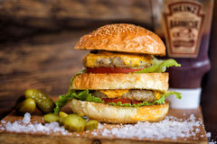 Delicious Homemade Maxi Burger with grilled beef steak, lettuce, cheese, tomato, onion, barbecue sauce, honey mustard, pickles Royalty Free Stock Photos