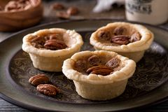 Mini Pecan Butter Tarts. Delicious homemade mini pecan butter tarts on a rustic table top royalty free stock image
