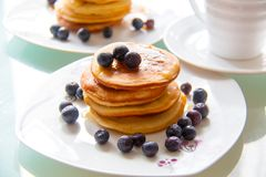 Delicious homemade pancake tower with maple sirup and organic blueberries on the white plate next the cup of coffee. Sweet breakfa royalty free stock photography