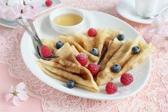 Delicious homemade pancakes with berries garnish and honey Stock Images