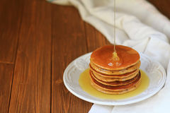 Delicious homemade pancakes. With honey on a brown wooden table Stock Image