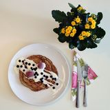 Delicious homemade pancakes with some yellow flowers on the background. Beautiful homemade pancakes served with yoghurt and berries. Also tableware and yellow stock photography