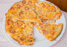 Delicious homemade pizza with cheese, sausage and tomatoes on a white plate Royalty Free Stock Photo
