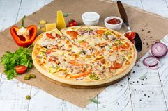 Delicious homemade pizza. Homemade cheesy pizza with pickled cucumbers, tomato, red onion rings and chicken meat. Fast food delivery concept. Copy space royalty free stock photography