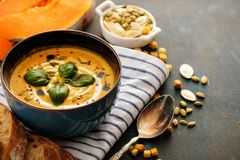 Delicious homemade pumpkin soup with basil leaves. Stock Photos