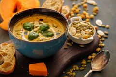 Delicious homemade pumpkin soup with basil leaves. Royalty Free Stock Image