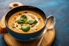 Delicious homemade pumpkin soup with basil leaves. Royalty Free Stock Photos