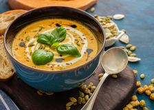 Delicious homemade pumpkin soup with basil leaves. Stock Images