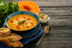 Delicious homemade pumpkin soup with prawns, chili and basil lea Royalty Free Stock Image