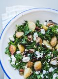 Delicious homemade roast potato, kale and feta cheese salad with nuts. Best thing to eat on a hot summery day is a yummy, healthy salad. With some kale tossed stock image