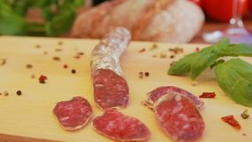 Delicious homemade salami jerky sausages on a wooden board. With basil stock footage