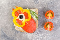 Delicious homemade smoked salmon canapes with cream, garnished w. Ith a fresh rosemary leaf on dark background. Seafood eating concept Royalty Free Stock Photography