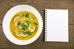 The delicious homemade Thai green curry with pork (Gang Keaw Wan) in white bowl and blank note book Royalty Free Stock Photos