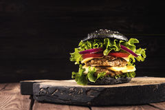 Delicious homemade vegan black burger with two chickpea cutlets, tomatoes, cheese, onion and salad on wooden table, dark Royalty Free Stock Photo
