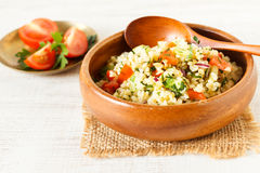 Homemade rustic bulgur salad. Delicious homemade vegetarian bulgur dish with vegetables and fresh herbs Royalty Free Stock Image