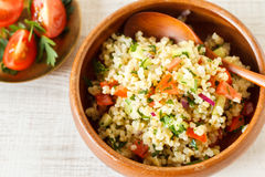 Homemade rustic bulgur salad. Delicious homemade vegetarian bulgur dish with vegetables and fresh herbs Royalty Free Stock Photo