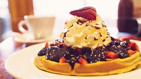 Delicious homemade waffle desert with fruits and whip creame Royalty Free Stock Images
