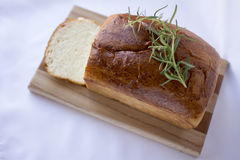 Delicious homemade white bread on wood cutting board above view. Delicious slices of  homemade white bread loaf on wood cutting board with rosemary on white Royalty Free Stock Photo