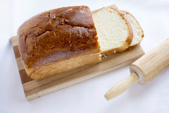 Delicious homemade white bread on wood cutting board selected fo. Delicious homemade white bread loaf on wood cutting board and wooden rolling pin Royalty Free Stock Image