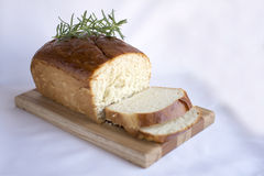 Delicious homemade white bread on wood cutting board. Delicious slices of  homemade white bread loaf on wood cutting board with rosemary on white fabric table Royalty Free Stock Image
