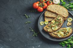 Delicious homemade whole grain rye sliced bread toast. With fried cutting mushroom champignon and onion on black ceramic plate, herbs and vegetables, dark royalty free stock image