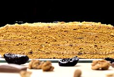 Delicious honey cake divided with prune and nuts on black background. stock photo
